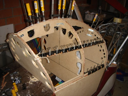 You see here a next mistake I made. I was placing the plates full with holes to place the clamps. Just count the holes. Euh ... I have 20 clamps. Understand the problem? So ... I decided to make the lamination two layers each time and staple the layers into the plates. You can also see that I made a line at the side. It is just a stick of 5 x 10 mm. I made small holes in the plates to glue it on its place. Give it some bending. The layers are easily clamped with paper-clamps on several places.