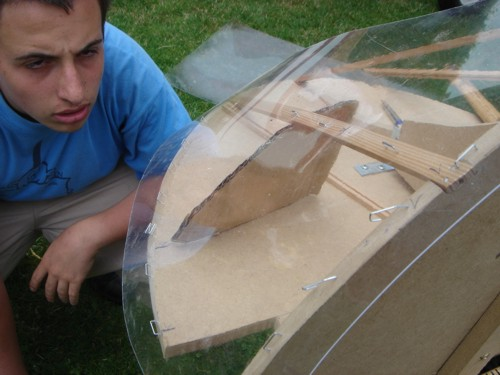 As you can see in the picture above. There are some struts and engine-mount tubes running through the place where the lexan should be. I wanted to solve that problem with making two extra lines to later place a tailor-cut plywood over it that will fit perfectly around those tubes. I will use rubber to make the final seals. Here Stefan uses a cardboard to test the ideal shape. A 0,75 mm plexi is placed as lexan-replacer.